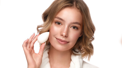 Beautiful tender young girl in a white coat with clean fresh skin posing in front of the camera with a sponge in her hands. Beauty face. Skin care.
