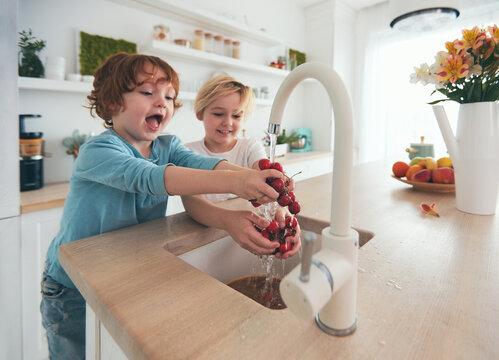 happy kids washing cherries under tap water at the kitchen