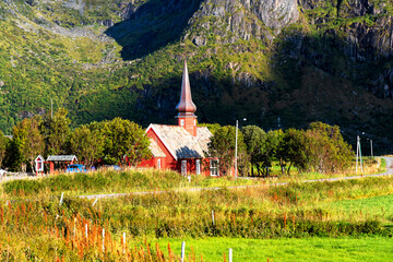 Flakstad Church with mountains in the background, exquisite XVIII century baroque masterpiece in the Arctic, Flakstadoy, Lofoten Islands, North of the Arctic Circle, Norway