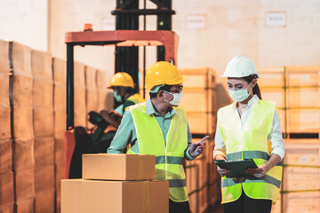 Asian engineers in helmet and face mask hold clipboard in warehouse