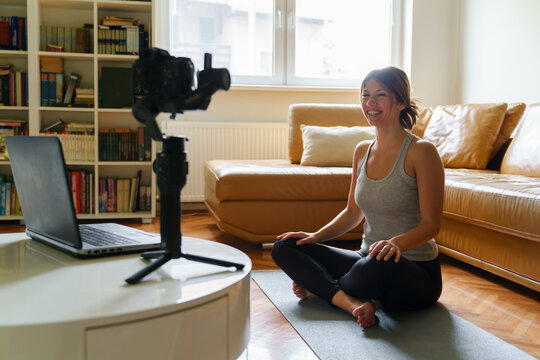 The new normal concept - Young adult caucasian woman sitting at home teaching yoga class in front of the camera and laptop - remote working during the covid-19 pandemic crisis - blogger work from home
