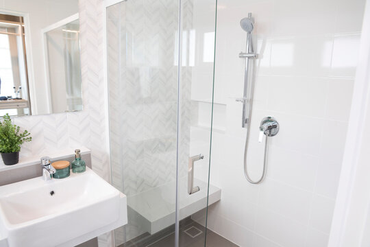 Shower room with chrome tap, transparent glass doors and a shelf. Apartment or hotel room.