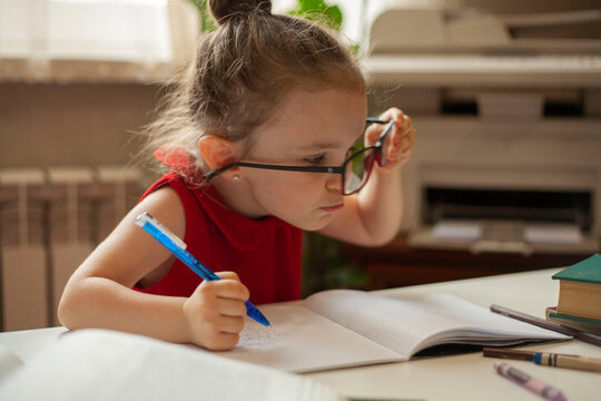 The girl raised her glasses with one hand and looks puzzled in front of her. International Literacy Day. Education and science. Distance learning. Preschool education.