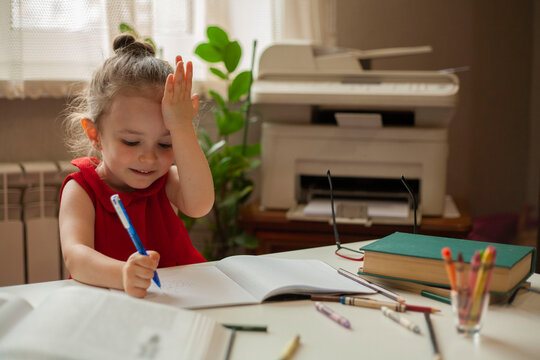 The girl writes with one hand in a notebook, and rests her other hand against her head. Made a mistake while learning lessons. International Literacy Day. Distance learning. Preschool education.