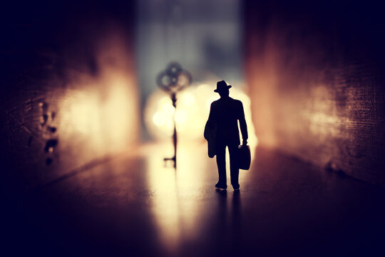 concept image of person walking towards bright light and finding the right key in dark path