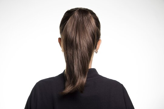 Back view of a female dark brown straight hair ponytail small earrings black shirt white background