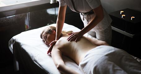 Young beautiful woman lying on massage table and enjoying massage.