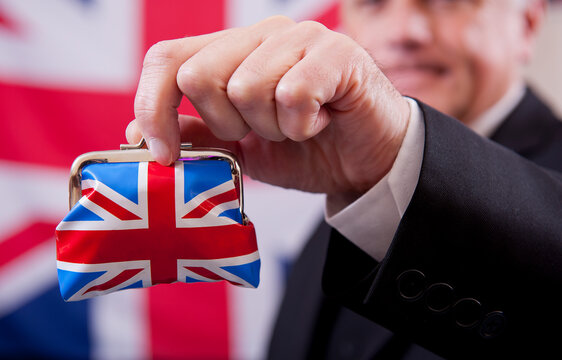 Stereotypical English businessman holding a Union Jack money purse. The man is wearing a dark business suit and bowler hat, with a Union Jack flag background.