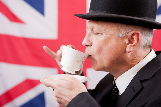 Englishman drinking afternoon tea from a cup and saucer, he's wearing a dark business suit with a bowler hat and standing against a Union Jack flag background.