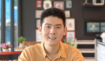 Portrait of happy smiling young business Asian, Chinese man person working from home and talking to his colleagues in webcam group video call conference on internet online in corona virus pandemic.