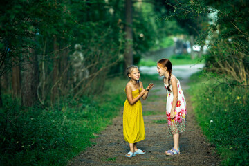 Two little girl friends have fun gossip in a pine Park.