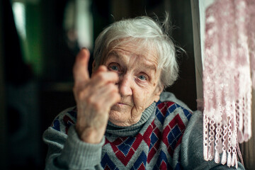 Portrait of an elderly woman indignantly wags her finger.