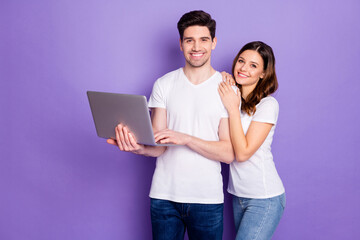 Portrait of positive couple man woman hold laptop work from home have online partnership...
