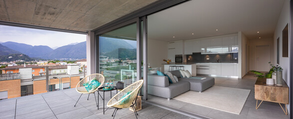 Large terrace with two armchairs or chairs. You can also see the interior of the modern apartment...