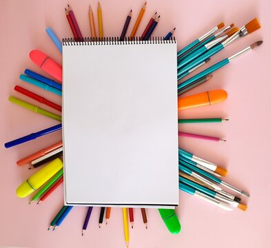 Paintbrushes, the colorful pencils, markers  under the painting journal