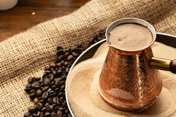 Turkish coffee prepared in sand with turk