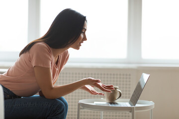 Woman Having Online Video Chat Sitting On Sofa At Home