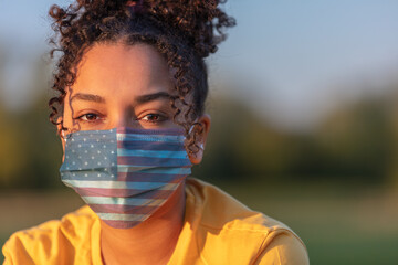 African American Teenager Girl Woman Wearing USA Flag Coronavirus COVID-19 Face Mask in Virus Pandemic
