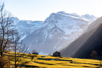 View of the Alps in Glarus, Switzerland, on a sunset evening with sun passing across the mountains