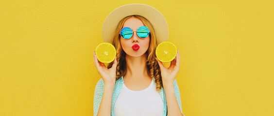 Summer portrait of young woman with fruits slice of orange blowing red lips sending sweet air kiss wearing straw hat on yellow background