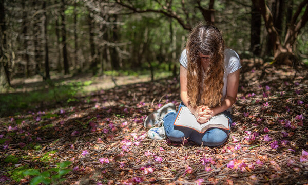 Young teen girl reading Bible alone in woods