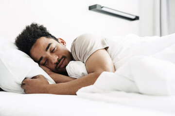 Photo of young african american man with mustache sleeping in white bed