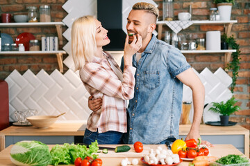 Beautiful young couple is feeding each other and smiling while cooking in kitchen at home