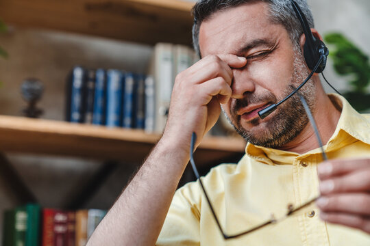 Close up of call center operator man wearing headset tired at home office