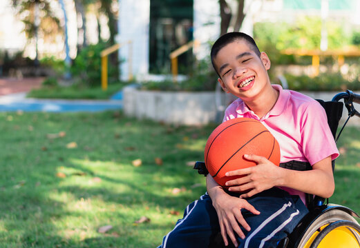 Asian special child on wheelchair is playing basket ball to strengthen muscles in the outdoor park, Lifestyle of disability child, Life in the education age, Happy disabled kid in homeschool concept.