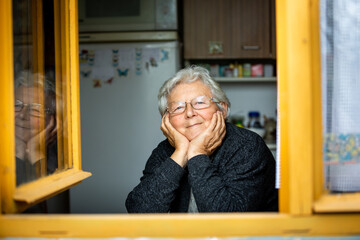 Portrait of lovely senior woman or grandmother watching out from the window and smiling, pensioner