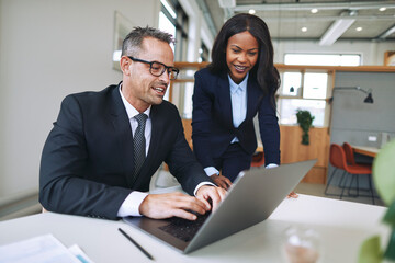 Two smiling businesspeople working on a laptop in an office