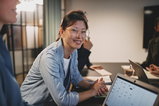 Smiling Asian businesswoman sitting with coworkers at an office
