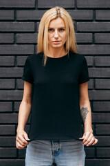 Stylish blonde girl wearing black t-shirt and glasses posing on black wall background, urban...
