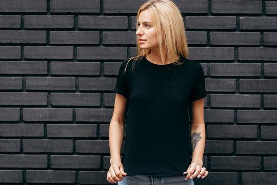 Stylish blonde girl wearing black t-shirt and glasses posing on black wall background, urban clothing style. Street photography