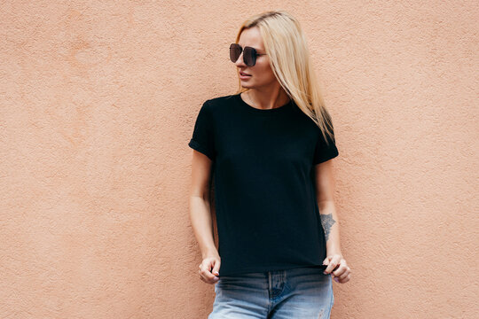 Stylish blonde girl wearing black t-shirt and glasses posing against street , urban clothing style. Street photography