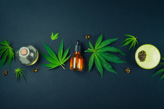 Medical CBD oil on black trendy background with cannabis leaves. The concept of medical tincture of marijuana. Trendy Flat Lay Minimalism Banner