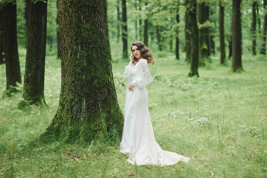 Portrait of a beautiful bride in a modest dress. Young brunette girl in a white dress with long sleeves. Cute bride with an autumn bouquet. Portrait of a woman outdoors on an autumn street.