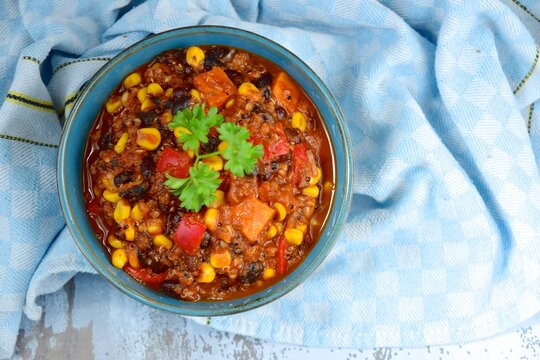 Black bean, quinoa, sweet potato, bell pepper and corn chili in a bowl garnish with parsley
