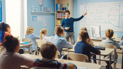 Caring Teacher Explains Lesson to a Classroom Full of Bright Diverse Children. In Elementary School...