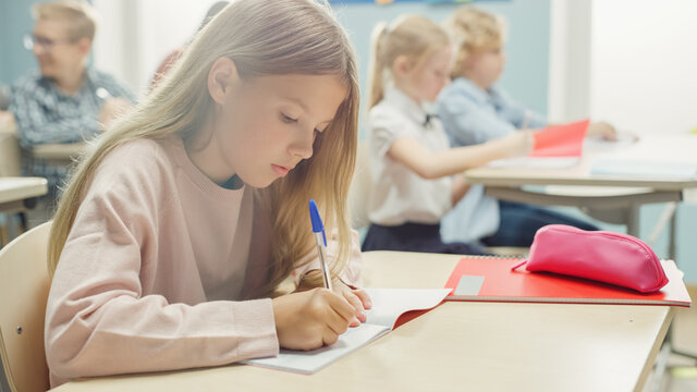 In Elementary School Classroom Caucasian Girl Writes in Exercise Notebook, Taking Test and Writing Exam. Junior Classroom with Diverse Group of Children Working Diligently and Learning New Stuff
