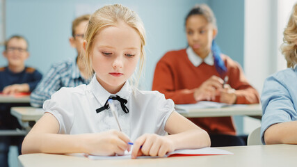In Elementary School Class: Portrait of a Brilliant and Cute Caucasian Girl Writes in Exercise...