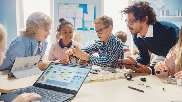 Elementary School Robotics Classroom: Diverse Group of Brilliant Children with Enthusiastic Teacher Building and Programming Robot. Kids Learning Software Design and Creative Robotics Engineering