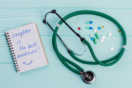 Notepad with medical stethoscope and near drug pills lying on blue background. Laughter is the best medicine on the notepad.