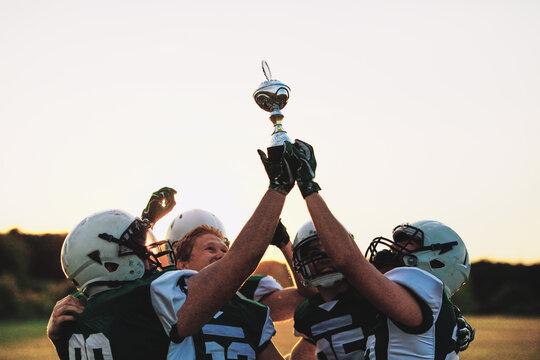 Cheering American football team lifting a championship trophy