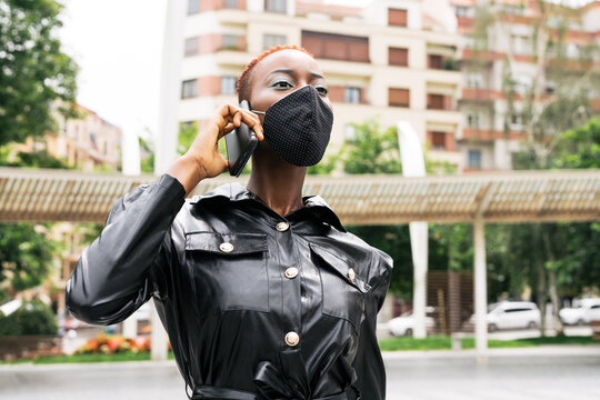 Beautiful black girl model business with mask talking on her cell phone