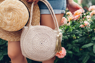 Stylish female purse and straw hat. Young woman holding beautiful summer accessories outdoors. City fashion