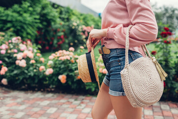 Stylish female handbag and straw hat. Young woman holding beautiful summer accessories outdoors. City fashion