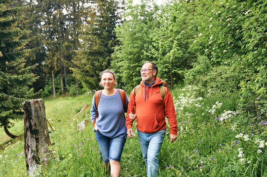 Middle age couple hiking in green forest, active family time