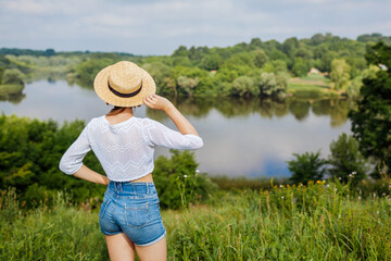 Woman enjoying walk in summer field by river. Girl admires lake landscape view. Holiday travel