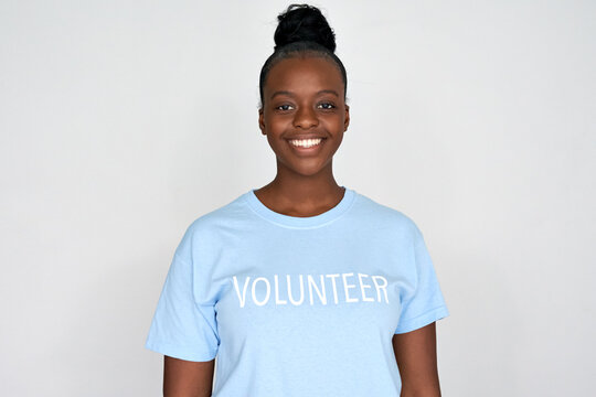 Happy young african american woman activist wear volunteer tshirt look at camera isolated on grey background. Charity organization, volunteer help donation service people support altruism concept.